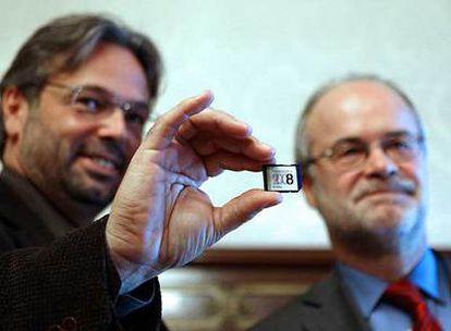 Castells entrega al presidente del Parlament, Ernest Benach, una tarjeta electrónica con las cuentas.