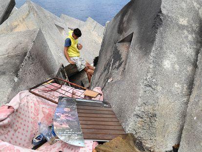 Dos menores se despiertan este julio en una chabola en la escollera de la playa de Ceuta, donde viven desde hace más de dos meses.
