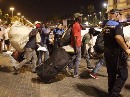 Un grupo de manteros se pasea por la zona del monumento a Colon ante la mirada de la policía portuaria.