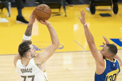 Luka Doncic lanza pese a la oposición de Stephen Curry.