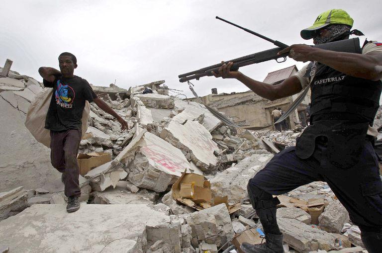 Un policía apunta a un haitiano con varios objetos cargados a su espalda.