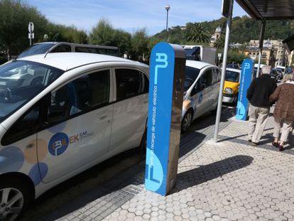 Dos de los coches eléctricos en alquiler situados junto a los postes de recarga en la calle Hernani de San Sebastián.