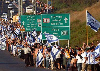 Centenares de ciudadanos israelíes forman la cadena humana a su paso por el enlace de carreteras de Latrun, en el centro de Israel.