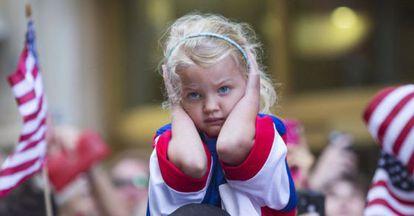 Una niña se tapa los oídos en el bullicio del recibimiento en Nueva York al equipo femenino de fútbol de Estados Unidos.