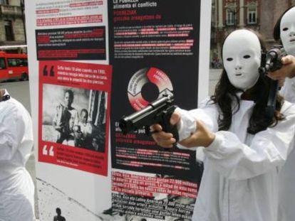 Acto de protesta llevado a cabo por miembros de la ONG Intermón-Oxfam en Bilbao, en protesta por el comercio incontrolado de armas.