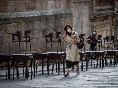 Una mujer pasa ante una terraza cerrada en Ourense, el 15 de octubre.
