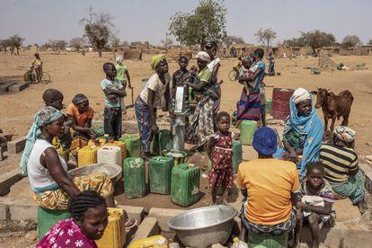 Mujeres y niños hacen cola para recoger agua en el campo de desplazados de Barsalogho, en Burkina Faso, en marzo de 2020.