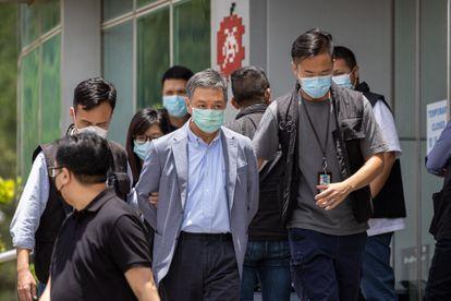 El director de operaciones del Apple Daily, Royston Chow Tat Kuen (centro), es escoltado por agentes de policía al salir de la oficina de Next Media, editor del Apple Daily, en Hong Kong (China), este jueves.