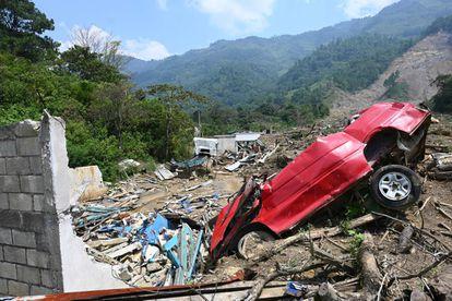 Un automóvil destruido en la aldea guatemalteca de Queja, que fue afectado por un deslizamiento de tierra provocado por las fuertes lluvias, efecto del cambio climático.