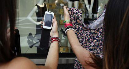 Dos mujeres buscan en internet el artículo que encuentran en un comercio.
