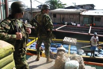 Integrantes de las fuerzas especiales del Ejército colombiano vigilan un bote que carga barriles para ser usados en laboratorios de cocaína.