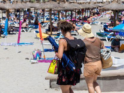 Dos personas llegan a la playa de Peguera, en Calvià (Mallorca), a principios de julio.