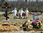 Cemetery workers wearing protective gear bury a coronavirus victim at a cemetery on the outskirts of Saint Petersburg on May 6, 2020. (Photo by OLGA MALTSEVA / AFP)