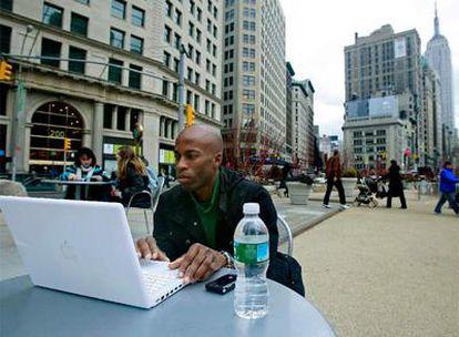 Estudiantes y transeúntes comparten espacio en una plaza peatonal en el centro de Manhattan, en Nueva York. Al fondo, el Empire State Building.