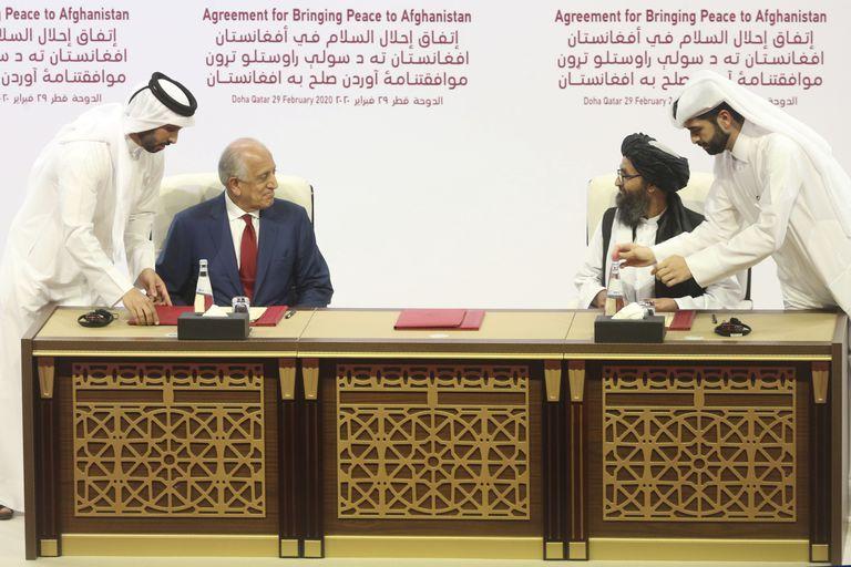 El embajador estadounidense Zalmay Khalilzad (izquierda) y el jefe negociador talibán, Abdulghani Baradar, en la firma del acuerdo para la retirada de las tropas norteamericanas de Afganistán, en Qatar el pasado febrero.