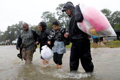 Una familia camina por el agua tras ser rescatada, el lunes.