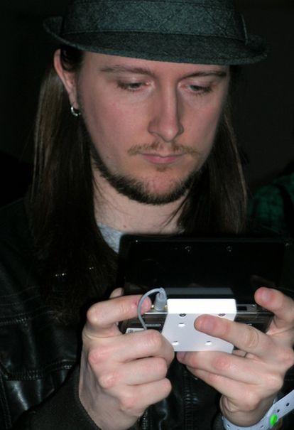 Un asistente a la presentación europea de la Nintendo 3DS juega con ella.