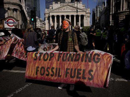 Un activista protesta frente al Banco de Inglaterra, en Londres, con una pancarta que pide el fin de la financiación para los combustibles fósiles.