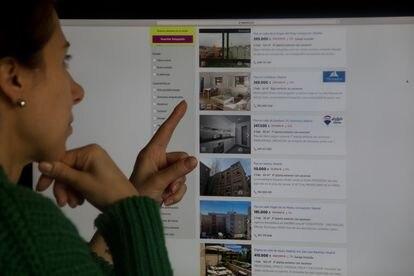 Una mujer consulta un portal inmobiliario con pisos rebajados, en Madrid.
