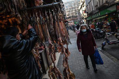Una mujer caminaba el martes cerca de un mercado de Wuhan.