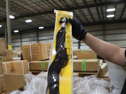 Un oficial de aduanas de EE UU inspecciona un cargamento de pelo humano procedente de China y confiscado en Nueva York, este 29 de junio.