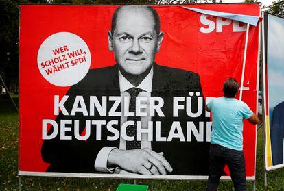 Un hombre pegaba el lunes en Bonn un cartel del candidato del SPD alemán, Olaf Scholz.