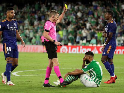 El árbitro Hernández Hernández enseña tarjeta amarilla al bético Nabil Fekir por simular un penalti ante el Madrid.