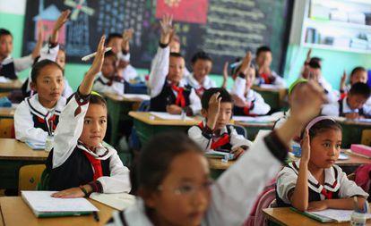 Los estudiantes de una clase de lengua tibetana levantan la mano para responder una pregunta en el colegio experimental de educación primaria de Lhasa, capital de la región autónoma de Tíbet, en junio de 2009.