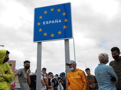 Varios migrantes esperan para pasar la frontera entre Ceuta y Marruecos voluntariamente.