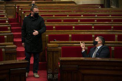 El diputado de la CUP, Vidal Aragones (izq.) conversa con el consejero de Interior, Miquel Sàmper, en el Parlament.