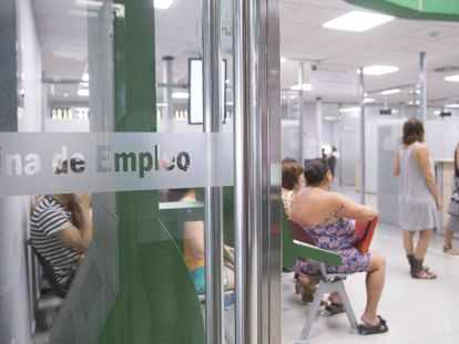 Varias personas esperan su turno en la oficina de empleo del barrio de Amate, en Sevilla.