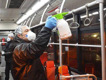 Personal de la empresa de autobuses iraní desinfecta un vehículo en Teherán.