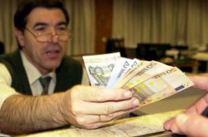 Un empleado de banca muestra unos billetes de euro. EFE/Archivo