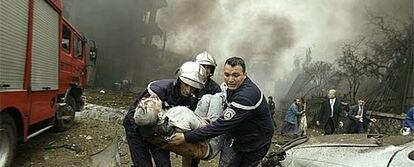Dos bomberos trasladan a un herido en los atentados de Argel