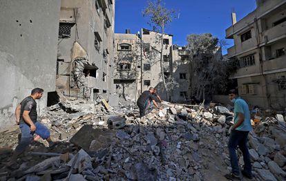 Habitantes de la Franja de Gaza buscan pertenencias entre los escombros de un edificio tras los ataques aéreos israelíes.