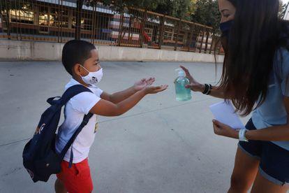 Un niño se protege con gel el primer día de curso en una escuela de Badalona.