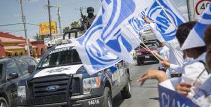 Una patrulla de la Policía Federal junto a simpatizantes del PAN.