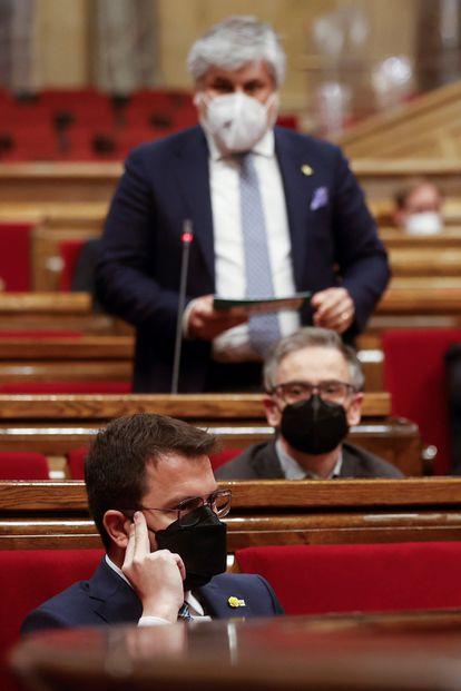 En primer plano, el 'presidente' Pere Aragonès, escucha al portavoz de JxCat, Albert Batet (al fondo), durante el pleno del Parlamento.