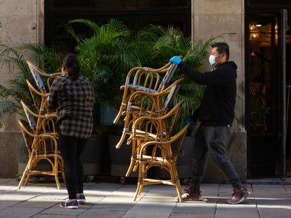 Dos trabajadores recogen la terraza de un bar del centro de Barcelona este viernes.