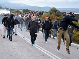 Un grupo de manifestantes lanzan piedras a los antidisturbios, este miércoles en Lesbos.