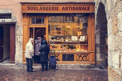 Algunos vecinos hacen cola en una panadería de la localidad francesa de Annecy.