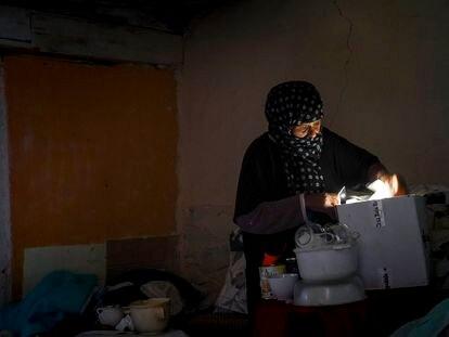 Ibilya busca papeles a la luz del móvil en el interior de su chabola en el sector VI de la Cañada Real.