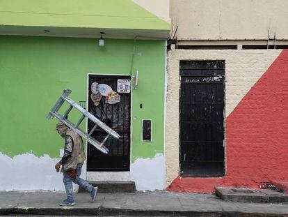 Un pintor de casas camina con una escalera mientras trabaja en las fachadas de la viviendas del cerro San Cristóbal, el 18 de Agosto de 2021, en Lima.