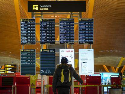 Un pasajero en el panel de salidas del aeropuerto de Barajas (Madrid), en diciembre.