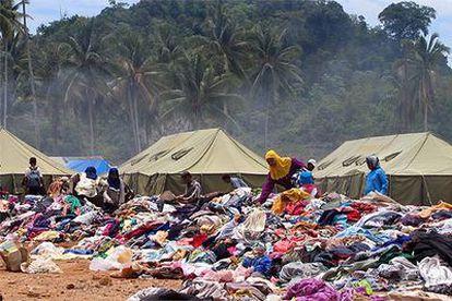 Habitantes de Calang rebuscan entre las montañas de ropa usada procedente de la ayuda internacional a pocos metros de un hospital de campaña.