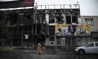 Dos personas caminan el lunes ante edificios quemados durante las protestas, en Teherán.