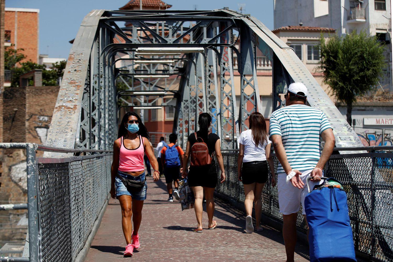 Unos vecinos cruzan el puente de la Torrassa, este sábado, en L'Hospitalet de Llobregat. EFE/Toni Albir