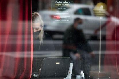 Una mujer dentro del bar Museo Chicote, en Gran Vía, 12. En el ventanal un cartel anuncia el cierre temporal del establecimiento.