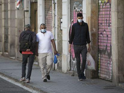 Tres personas se cruzan sin mantener la distancia de seguridad en una acera estrecha del barrio de Sant Atoni Abat, en el centro de Barcelona, el jueves. Albert García