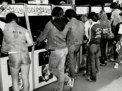 Un grupo de jóvenes juega con máquinas recreativas a principios de los ochenta.